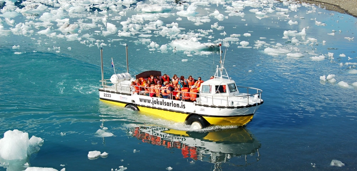 Glaciarlagoon in Iceland with iceblocks and a boat with many people from above