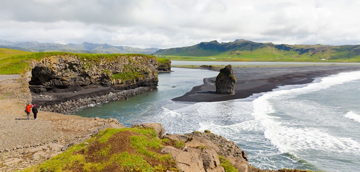 Two people walking in long distance close to a black beach in Iceland
