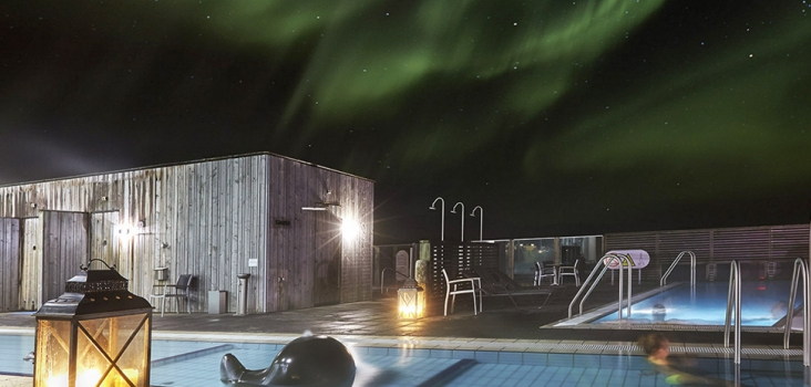 Night picture with green northern lights of an outside spa in Iceland